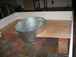 How about here. I measured and cut a hole in the false bottom for the bucket.